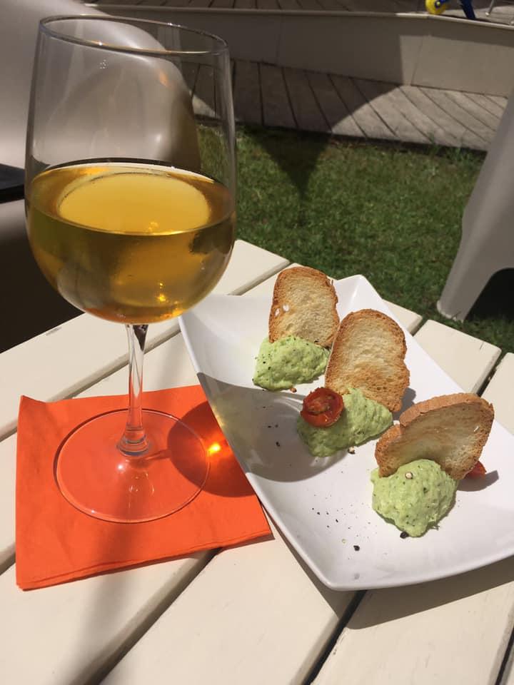 un calice di vino bianco e un piatto dicucina di pesce